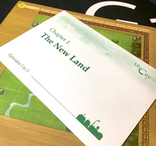 """Player board for My City with a large white envelope covering most of the board. Envelope is printed with """"Chapter 1: The New Land""""."""
