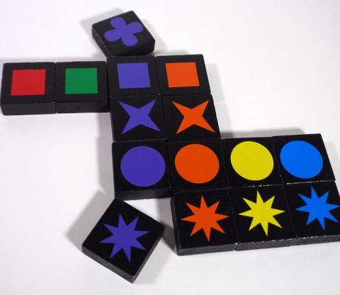 Qwirkle in play - adding two purple tiles