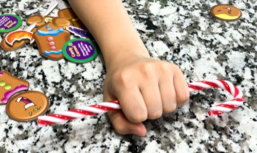 Child's hand grabbing plastic candy cane