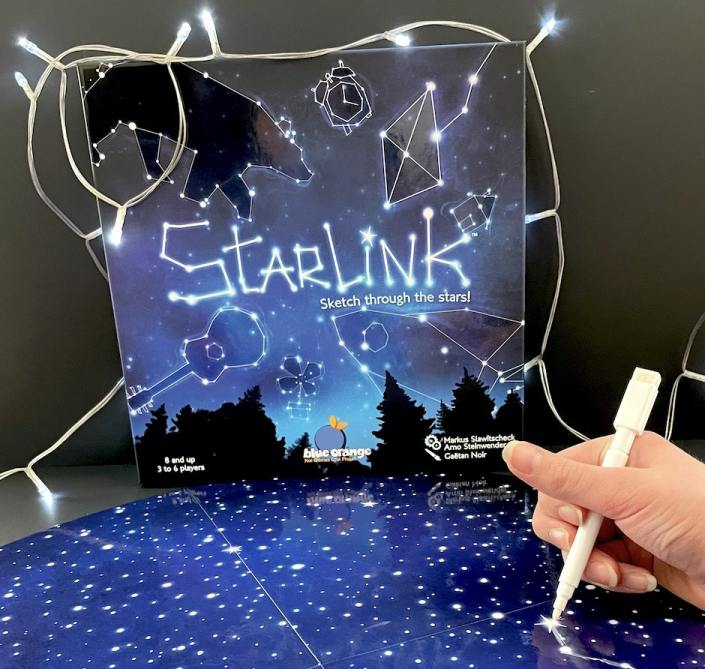 Starlink - Sketch through the stars!A hand holding a marker and drawing on the dark blue star board.