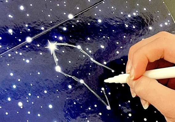 A hand drawing a rocket on a board full of stars