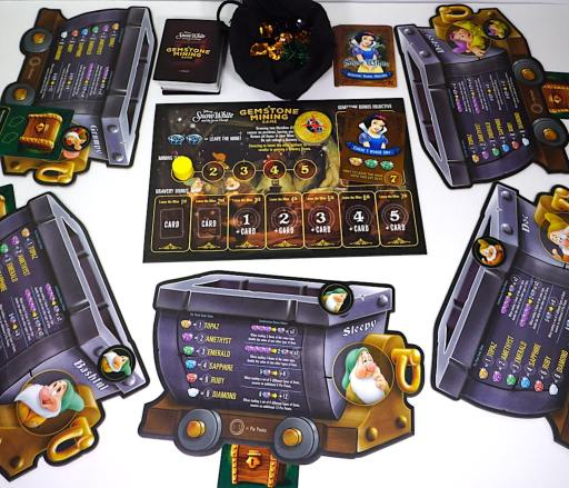 "5 dwarf mining cart boards around a central area: in the center, a bag of gems, 2 decks of cards, and a board with ""days"" and ""bravery bonuses"" marked."