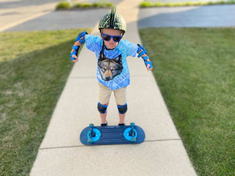 Boy with a skateboard balanced on his feet, leaning towards the camera