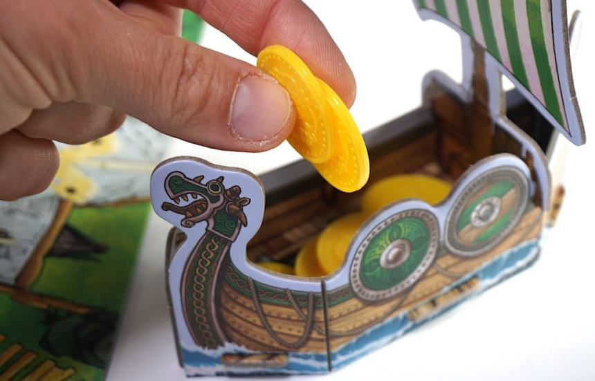 Fingers placing coins into a green boat