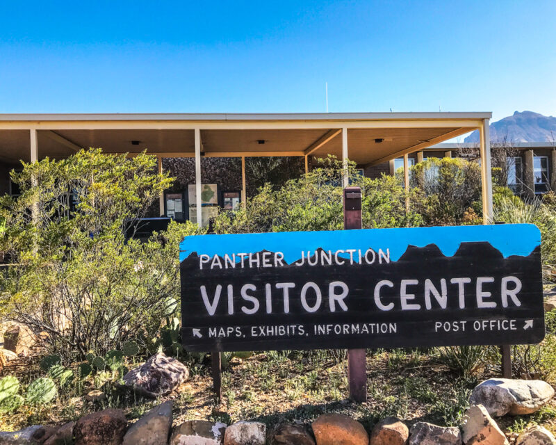 Panther Junction visitor center at Big Bend National Park, Texas; painted sign and green shrubs in foreground, low flat building and blue sky in background