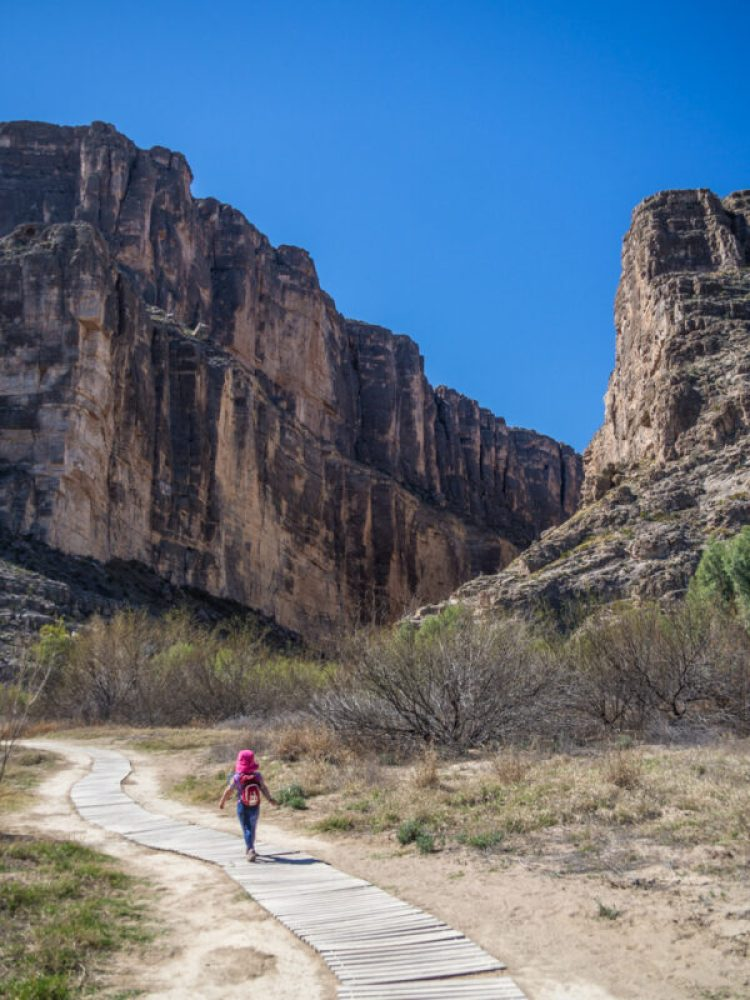 Young girl in pink hat hiking in Santa Elena Canyon, Big Bend National Park, Texas