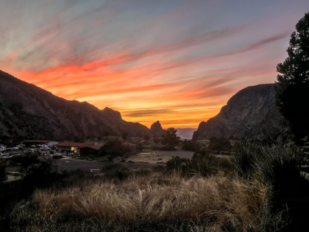 Orange and pink sunset over the Chisos developed area in Big Bend National Park, with Chisos mountains in the background