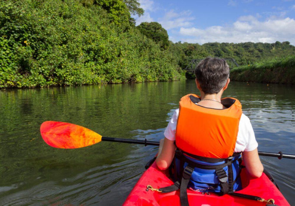 Retired caucasian lady in a red canoe or sea kayak on Hanalei river approaching the old steel bridge in Kauai