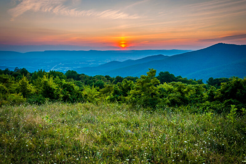Sunset over a meadow at Pass Mountain Overlook, Skyline Drive, Shenandoah National Park, Virginia.