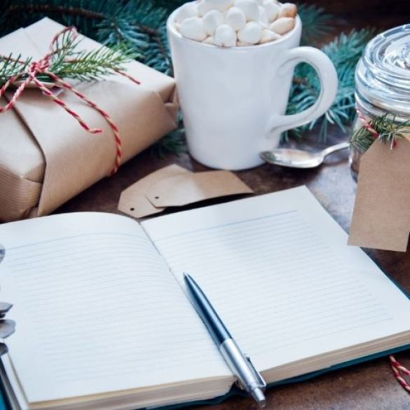 a notebook, hot chocolate and wrapped gift signifies a simple Christmas