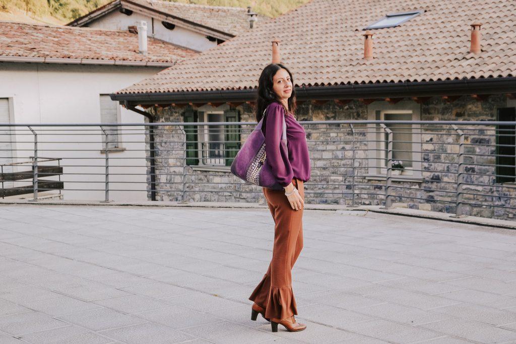 Come creare un outfit con quello che hai nell'armadio: Isabella The Fashion Cherry diary indossa dei pantaloni color zucca e una blusa color prugnaIsabella-The-Fashion-Cherry-diary-e-seduta-su-una-scalinata-e-indossa-dei-pantaloni-color-zucca-una-blusa-color-prugna-e-una-borsa-di-Gucci