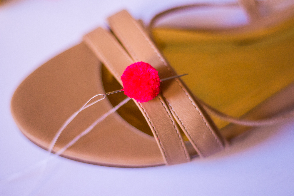 Wrap thread around one strap of the sandal. Stick the needle back through the pom.