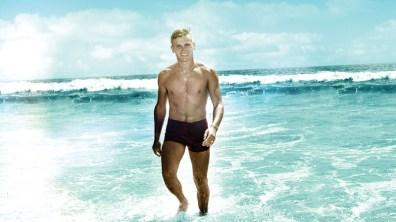 Shirtless, Tab Hunter hits the beach.