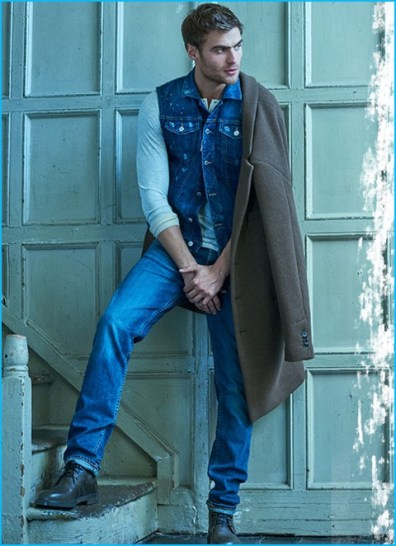 George Alsford layers with denim, wearing a single-breasted Barena coat with a Dsquared2 denim vest, Merz B. Schwanen henley, and Giorgio Armani leather boots.