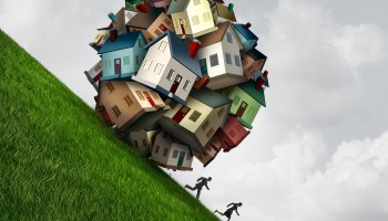housing crisis as a group of family homes shaped as a dangerous falling ball as a symbol for a housing or house construction industry problem with 3D illustration elements.