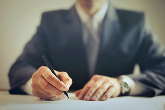 Key Considerations When Emigrating - man signing a contract image