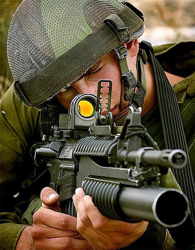 Un soldado usando una mira reflex.