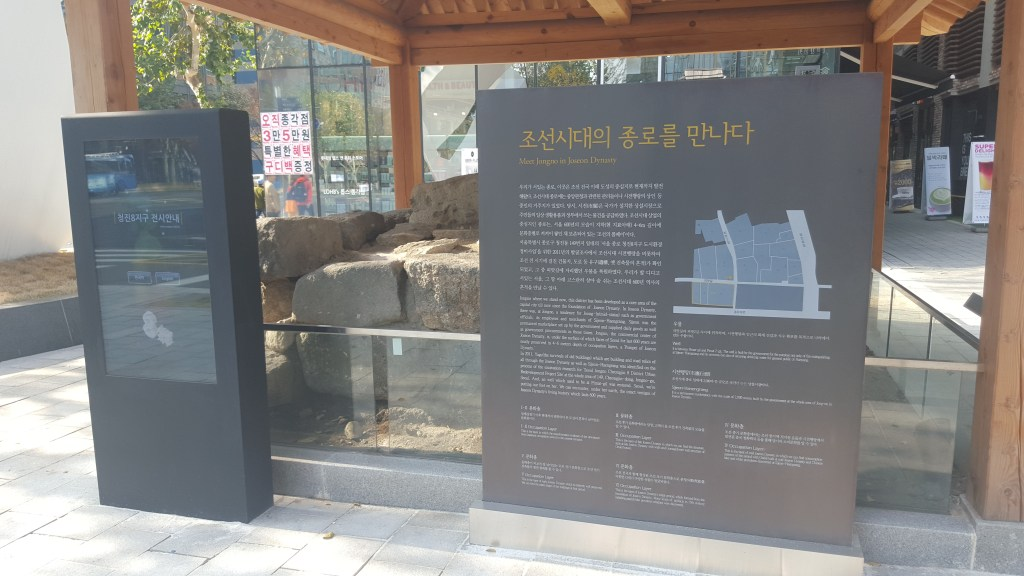 A carefully-preserved ancient well in the centre of Seoul's business district, and its interactive electronic information board in five different languages