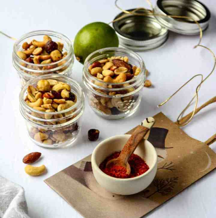 Three glass jars of mixed nuts on a table