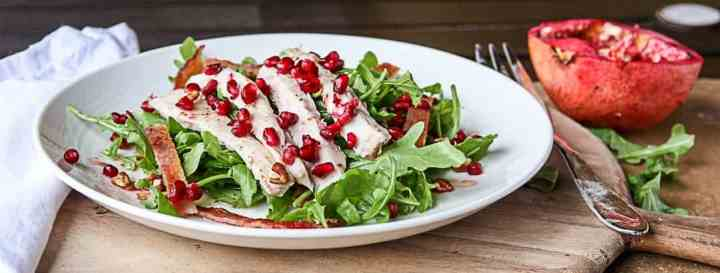 A plate of food on a table, with Salad and Pomegranate