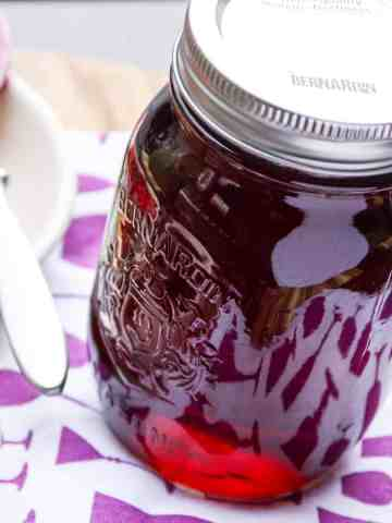 A jar of homemade grape jelly on a purple and white kitchen towel.