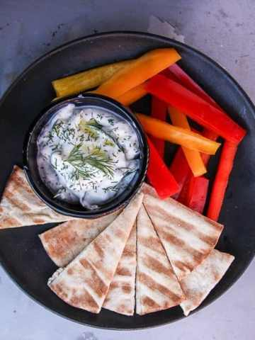A bowl of food on a plate, with Tzatziki