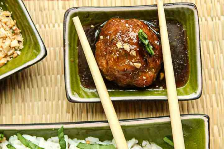 A meatball is being dipped in sauce using chopsticks