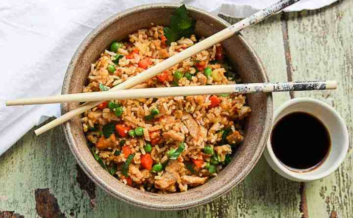 A bowl of fried rice and vegetable with chopsticks