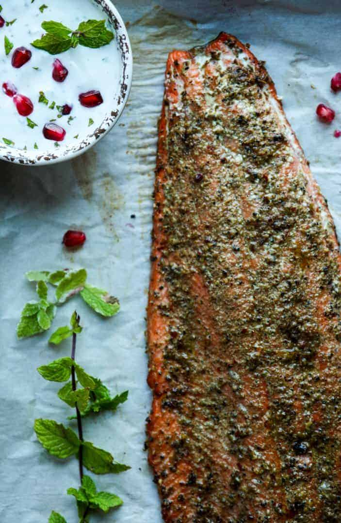 Baked fillet of salmon rubbed in spices with a sprig of mint and a small dish of raita