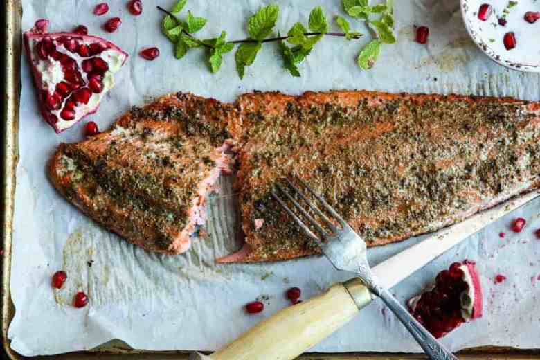 A cut piece of baked salmon on a tray with a knife and fork