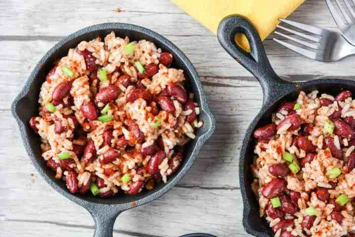 Red beans and rice in small black skillet on wooden table