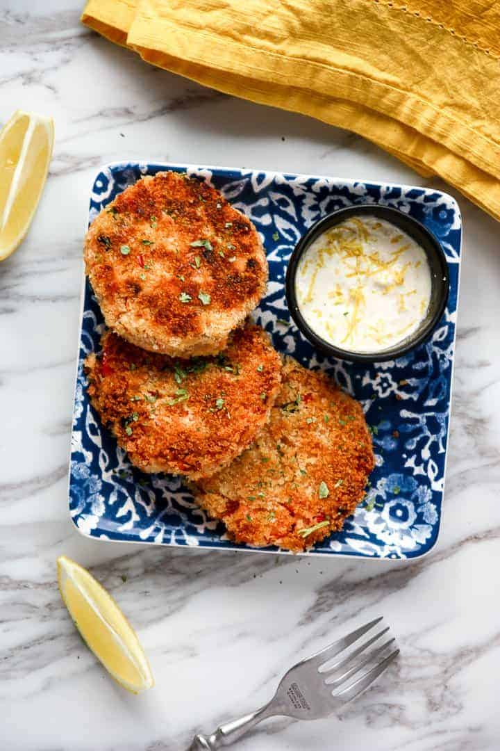Three salmon patties with side sauce on blue floral plate, atop white granite countertop