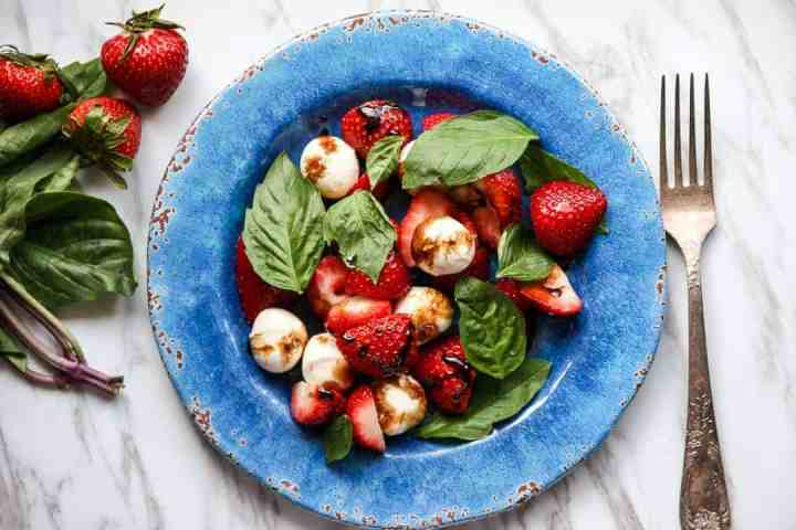 Top shot of basil, strawberries and mozzarella cheese balls on blue plate.