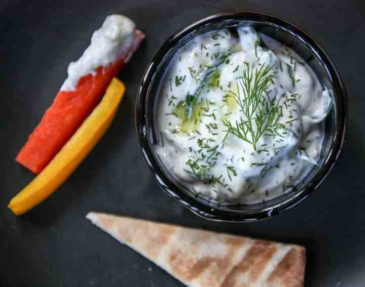 A bowl of food on a plate, with Tzatziki and Cucumber