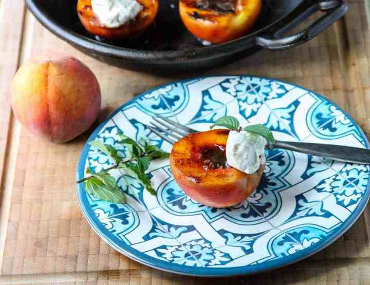 A grilled peach on a plate, with a fork