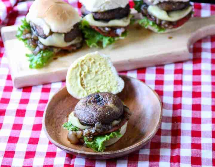 A plate of sliders on a table with mushrooms and cheese