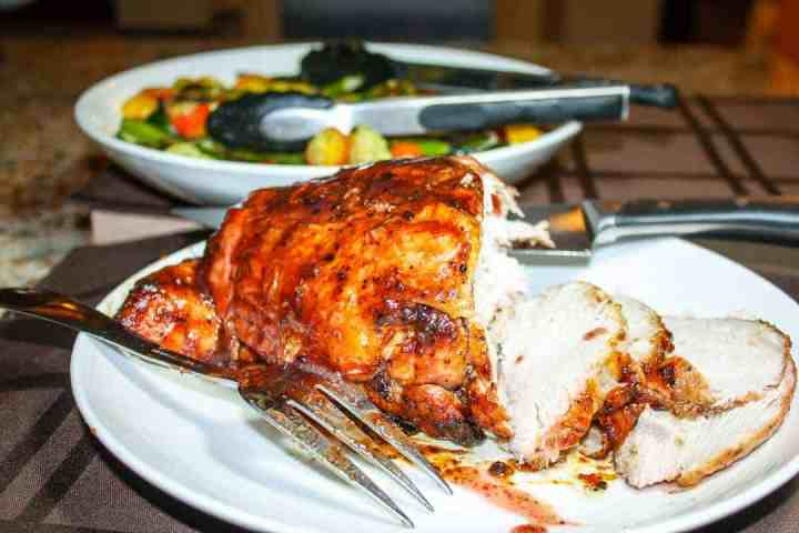A cooked turkey breast is getting sliced