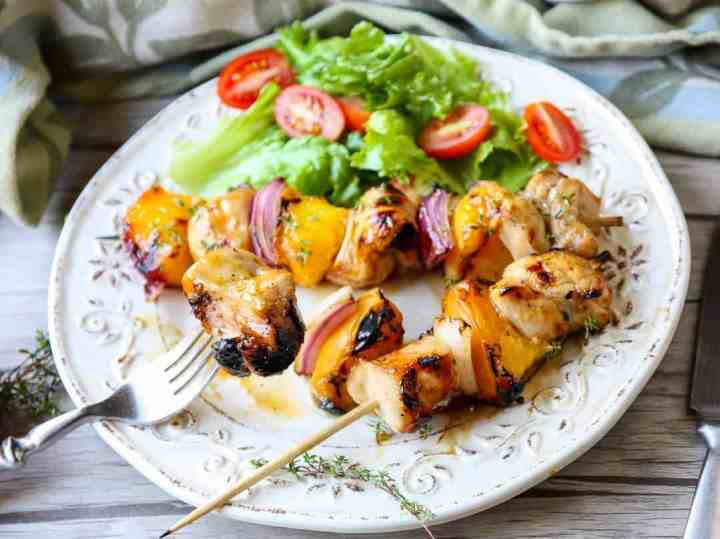 A plate of food on a table, with chicken and peaches