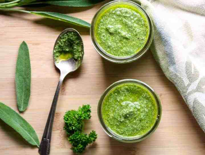 Two half pint jars of walnut sage pesto with sage and parsley leaves