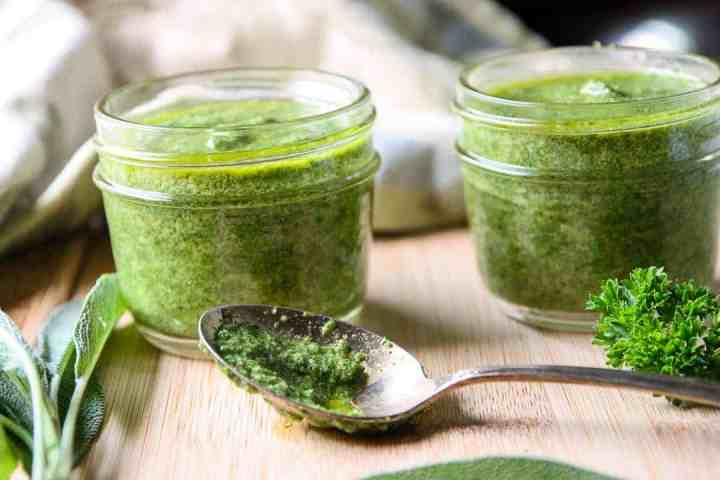 A jar of pesto on a cutting board with a spoon