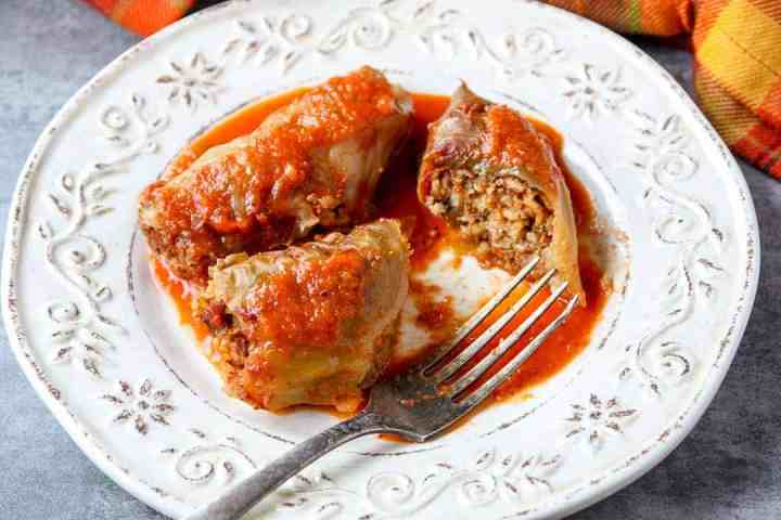 Three cabbage rolls with tomato sauce on an embossed white plate with a fork.