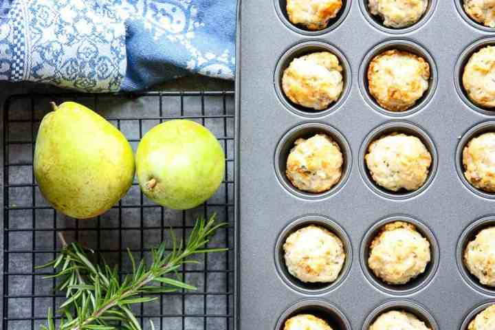 Mini muffin pan of pear gorgonzola appetizer bites with two pears and a sprig of rosemary
