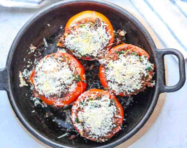 Four stuffed tomatoes in a skillet