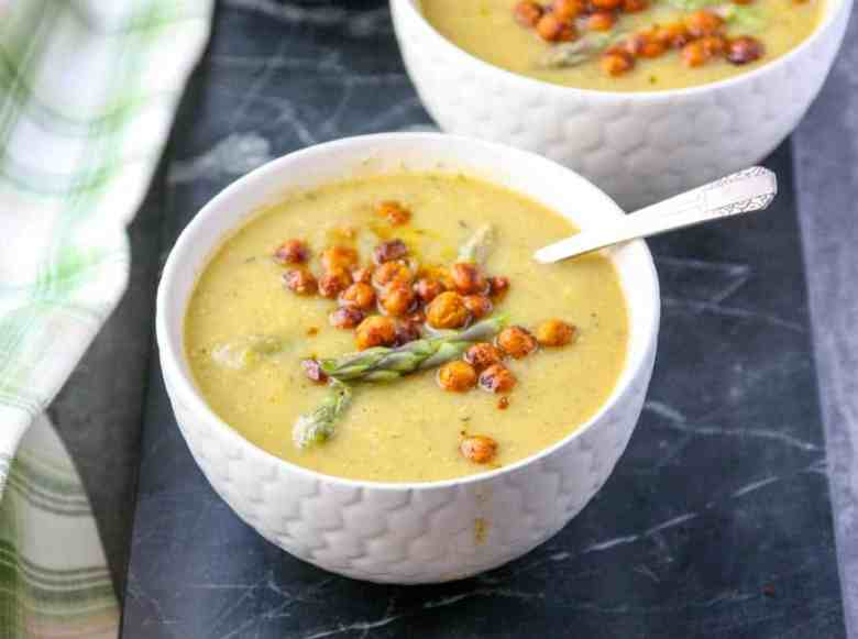 Creamy asparagus soup in a white bowl topped with roasted chickpeas & asparagus spears