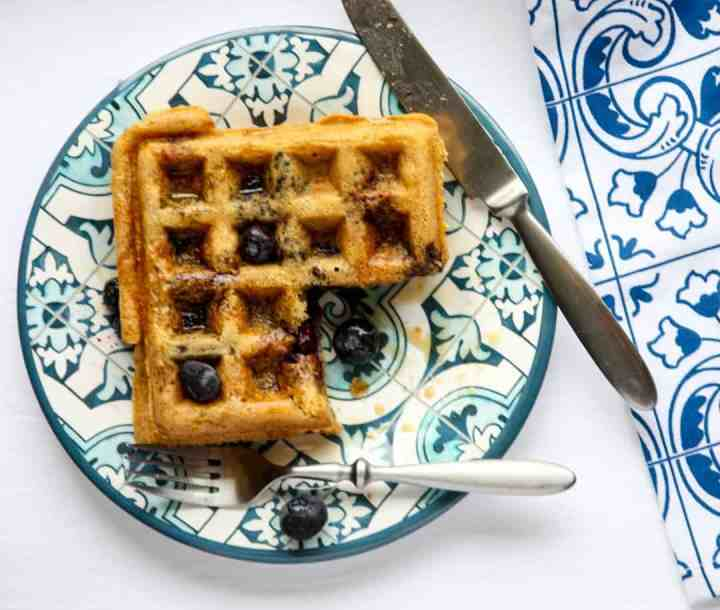 A waffle on a plate with a slice cut out of it