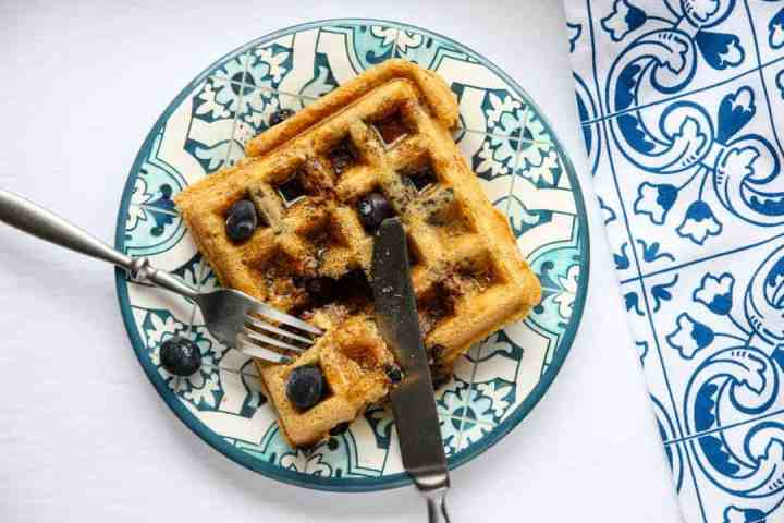 A waffle on a plate with a knife and fork