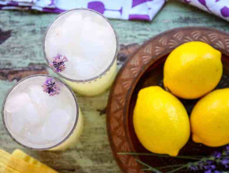 A bowl of lemons on a table, with Lavender sprigs