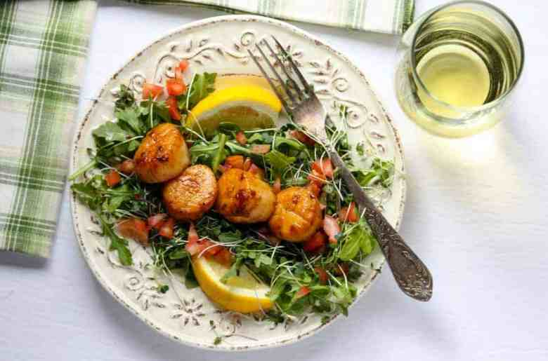 A plate of food on a table, with Scallops and Chardonnay
