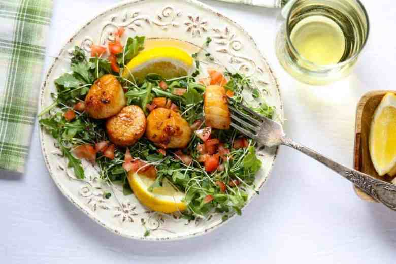 Four large seared scallops on a bed of microgreens on a white embossed plate with two lemon wedges