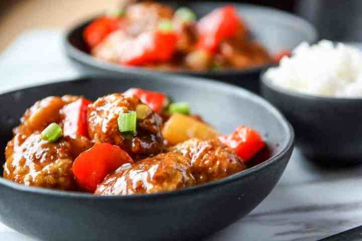 A close up of a bowl of meatballs with vegetables
